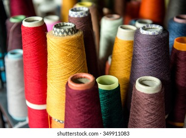 Colorful assortment of vivid colors of cotton spools on cardboard cones for use in the knitwear and garment industry viewed high angle
