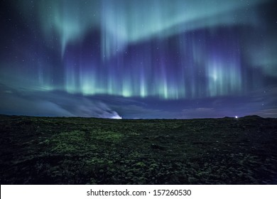 Colorful aurora over a mossy Icelandic lava field