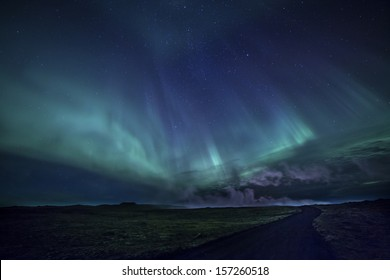Colorful aurora over a road through an Icelandic lava field.