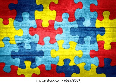 A colorful autism awareness puzzle background with wood texture illustration.