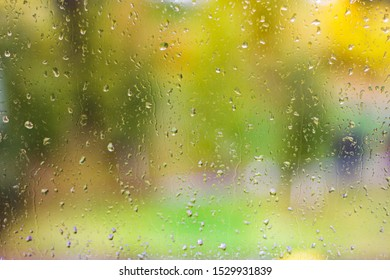 Colorful autumn background with raindrops on the window, wet glass after the rain with colored bunnies and reflexes, the surface is wet from the downpour with drops and streams of water.