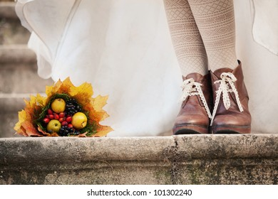 colorful autumn bouquet and two women legs with leather boots, closeup