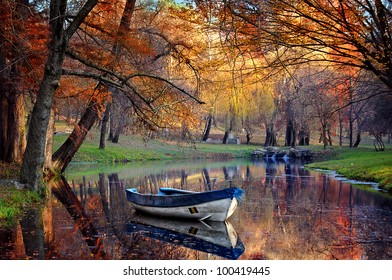 Colorful autumn landscape.Nature background.Boat on the lake in the autumnal forest