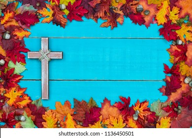 Colorful autumn leaves border with old religious cross hanging on rustic antique teal blue wood background; seasonal religion sign with copy space
