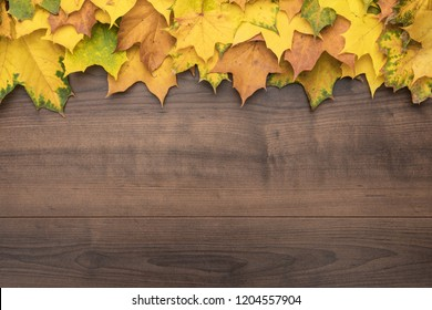 colorful autumn leaves on brown table. fall season concept background
