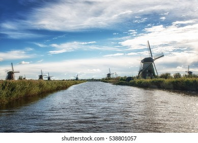 Colorful Autumn morning on the canal in Netherlands. Dutch windmills at Kinderdijk, an UNESCO world heritage site.
