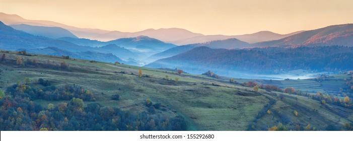 Colorful autumn panorama of the mountains. Sunrise