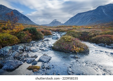 Colorful autumn tundra and mountain ridge behind the Malaya Belaya river stream in Hibiny mountains above the Arctic Circle, Russia