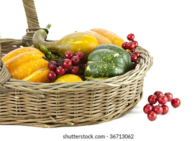Colorful Autumn Vegetables and Berries in woven  Basket isolated on white