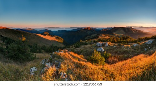 Colorful autumn in Velka Fatra hills with yellow grass mountain meadows lightened with warm sunrise light with cloudless blue sky and mist and fog in the valleys