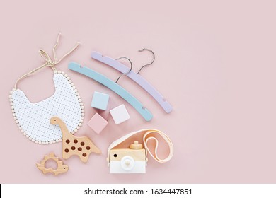 Colorful baby hangers, bib with wooden toys and teether. Set of baby stuff and accessories for newborn on pastel pink background.  Baby shower concept.  Flat lay, top view