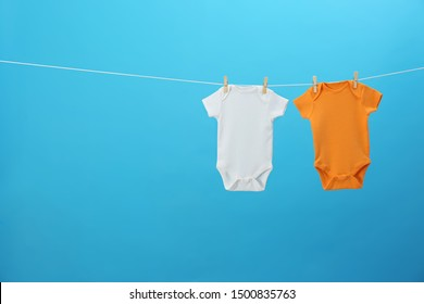 Colorful baby onesies hanging on clothes line against blue background, space for text. Laundry day