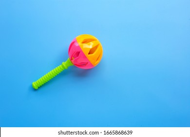 Colorful baby rattle on blue background. Copy space