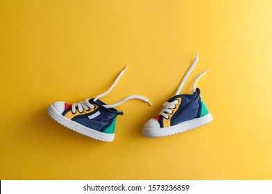 Colorful baby shoes on bright yellow background in child's room