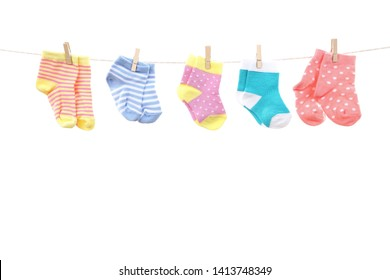 Colorful baby socks hanging on white background
