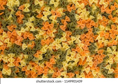 Colorful background of dried three color farfalle or bow tie pasta in a full frame view for use in Italian, vegan or vegetarian cuisine
