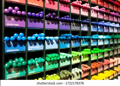Colorful background with multi-colored pencils placed on rack in art and crafts store, three quarter angle view