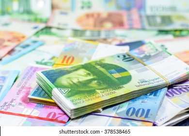 Colorful background with swiss franc currency,money.Focus on eye of top banknote and blurry on euro background