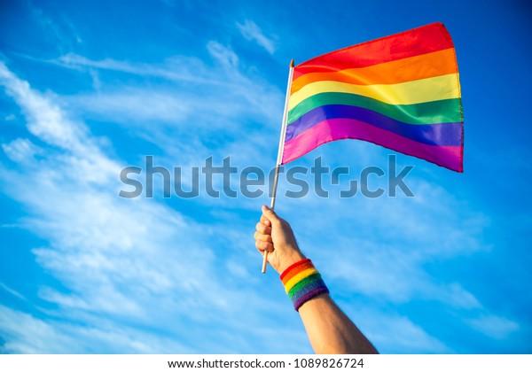 Un drapeau coloré à l'arc-en-ciel rétro-éclairé de la gay pride est brulé dans la brise contre un ciel au coucher du soleil.