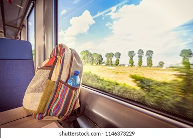 Colorful backpack on the train near the window. Conceptual image about traveling on vacation.