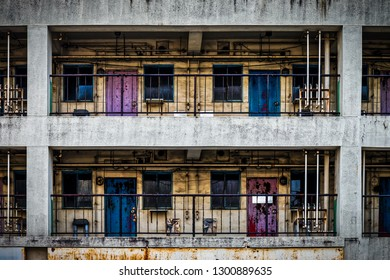 The colorful backside of a building with pipes, red and blue doors, and yellow paint in Yokosuka, Japan.