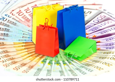 colorful bags over euro currency banknotes background. money and shopping concept