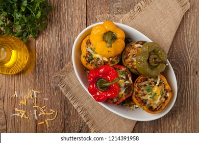 Colorful baked with cheese, stuffed peppers with rice and minced meat. Top view. Natural wooden background.
