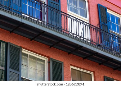 Colorful balconies line the streets in the French Quarter of New Orleans Louisiana. Close-up view of red building with balcony.