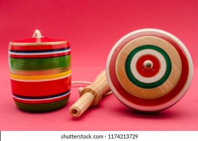 Colorful balero and yo yo against red background. Mexican wooden toys