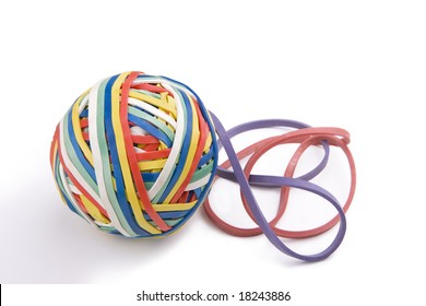 Colorful ball of rubber bands and two loose rubberbands on the side.  On a white background.