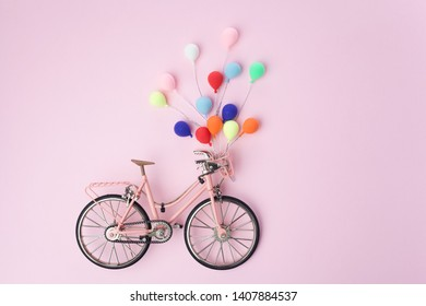 Colorful balloon hang the pink bicycle vintage on pink pastel background. idea of love. Minimal love concept.