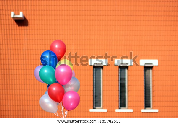 Colorful balloon and orange wall