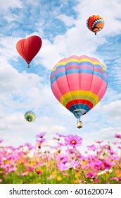 Colorful balloon over bright sky with clouds.