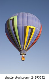 colorful balloon rising at dawn in the cold air at the Taos hot air balloon festival
