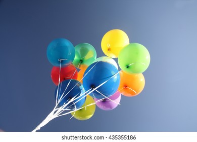 Colorful balloons in a bright blue sky