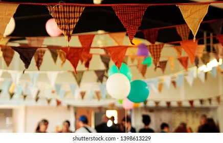 Colorful balloons and bunting hang from the beams as a party takes place beneath.