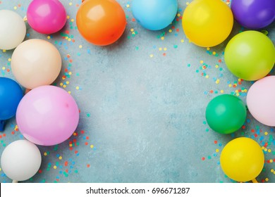 colorful balloons and confetti on blue table top view festive or party background flat