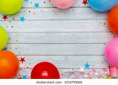Colorful balloons and confetti on wooden table top view. Festive or party background. Flat lay style. Birthday greeting card. Carnival.