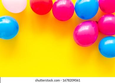 Farbige Ballons auf gelbem Hintergrund, Kopienraum im oberen Rahmen