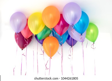 Colorful balloons in the interior of a white room background