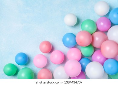 Colorful balloons on blue table top view. Birthday or party background. Flat lay style.