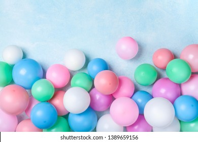 Colorful balloons on blue table top view. Festive or party background. Flat lay style. Birthday greeting card.