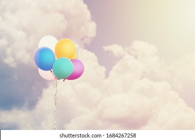 Colorful balloons on cloud and sky background