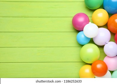 Colorful balloons on green wooden table