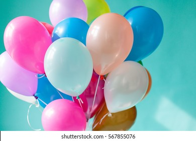 Colorful balloons on the mint background