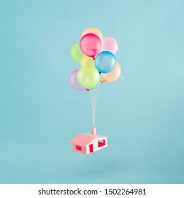 Colorful balloons with pink house flies in the blue sky. creative concept.
