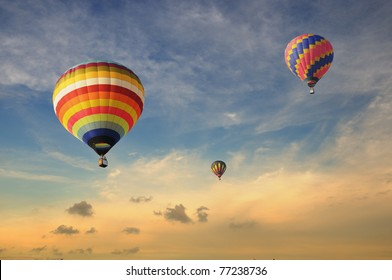 Colorful balloons rising up during sunset