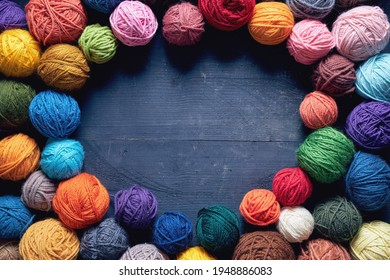 Colorful balls of wool on wooden table. Variety of yarn balls, view from above.