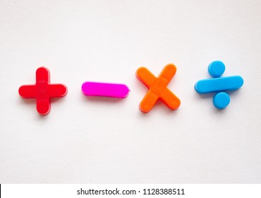 Colorful basic mathematical symbols, made of plastic. The set comprised plus, minus, multiplication, and division, and placed on a white background.
