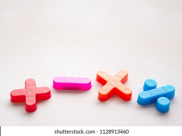 Colorful basic mathematical symbols, made of plastic, taken with a selective focus. The set comprised plus, minus, multiplication, and division, and placed on a white background.